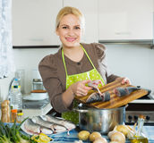 Smiling woman cutting white fish Royalty Free Stock Photography