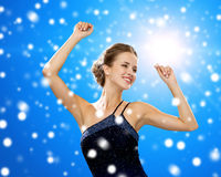 Smiling woman dancing with raised hands Stock Images