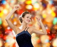 Smiling woman dancing with raised hands Stock Photo