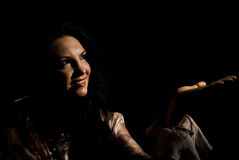 Smiling woman in dark make a presentation. Beautiful woman standing with  hand open and showing the copy space or presenting something to lighting,soft light on Stock Images