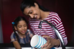 Smiling woman with daughter washing cup at sink. Smiling women with daughter washing cup at kitchen sink at home Stock Image