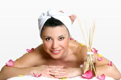 Smiling woman day spa. Smiling woman wearing head turban relaxes amongst fragrant rose petals and aroma sticks Stock Image