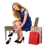 Smiling woman deciding on a new pair of shoes. Smiling woman trying to decide on a new pair of shoes as she sits on a seat in a store with her shopping bags Royalty Free Stock Photos