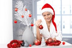Smiling woman decorating for christmas stock images