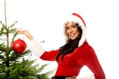 Smiling woman decorating christmas tree Royalty Free Stock Image