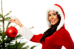 Smiling woman decorating christmas tree Royalty Free Stock Photography