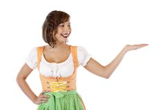 Smiling woman with dirndl looks at empty palm Royalty Free Stock Images
