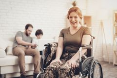 Smiling Woman. Disabled Soldier In A Wheelchair. Meeting After War. Son And Husband Background. Camouflage Uniform. Family Background. Paralyzed Soldier. Home royalty free stock image