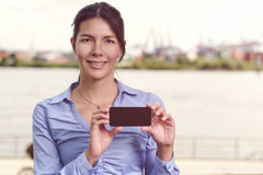 Smiling woman displaying her mobile phone Stock Photo