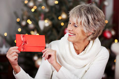 Smiling woman displaying a red Christmas voucher. Smiling stylish elderly woman displaying a red Christmas voucher in her hands in front of a twinkling Christmas royalty free stock photography
