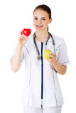Smiling woman doctor with a green apple and red heart. Stock Images