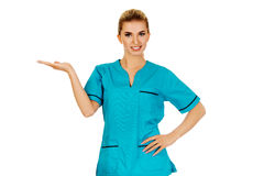 Smiling woman doctor or nurse pointing something Royalty Free Stock Images