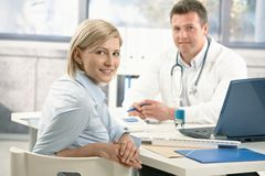 Smiling woman in doctor's office royalty free stock images