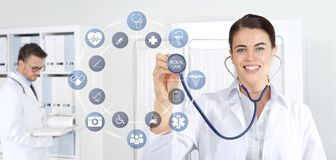 Smiling woman doctor with stethoscope pointing medical symbols icons on medical clinic background royalty free stock photos