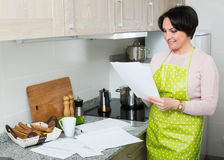 Smiling woman with documents in kitchen Stock Photo