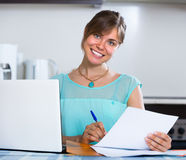 Smiling woman with documents at kitchen Royalty Free Stock Image