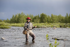 Smiling woman does fly fishing Royalty Free Stock Images
