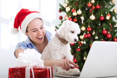 Smiling woman with dog looking to computer and surprised Royalty Free Stock Images