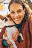 Smiling woman with dog outdoors in autumn making selfie. Smiling young woman with small dog outdoors in autumn making selfie Stock Photo