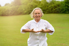 Smiling Woman doing breathing exercises. Single beautiful senior woman in white rolled up long sleeve blouse practicing breathing exercises outside on green Stock Image