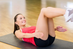 Smiling woman doing exercise on mat in gym Royalty Free Stock Image