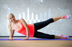 Smiling woman doing exercises on mat in gym Royalty Free Stock Image