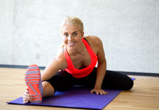 Smiling woman doing exercises on mat in gym Royalty Free Stock Images