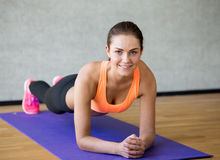 Smiling woman doing exercises on mat in gym Stock Images