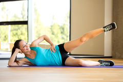 Smiling woman doing exercises on mat in gym Royalty Free Stock Photography
