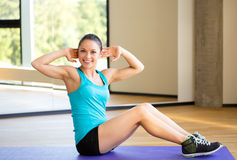 Smiling woman doing exercises on mat in gym Stock Image