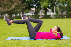 Smiling woman doing exercises on mat outdoors Stock Photo