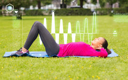 Smiling woman doing exercises on mat outdoors Stock Photography