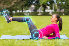 Smiling woman doing exercises on mat outdoors Stock Photos