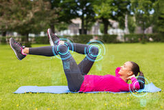 Smiling woman doing exercises on mat outdoors Royalty Free Stock Image