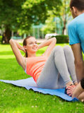 Smiling woman doing exercises on mat outdoors Royalty Free Stock Images