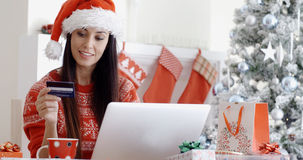 Smiling woman doing online Christmas shopping Royalty Free Stock Images