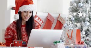 Smiling woman doing online Christmas shopping stock video footage