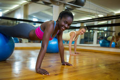 Smiling woman doing pilates exercises on fitness ball with coach in fitness studio Royalty Free Stock Image