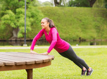 Smiling woman doing push-ups on bench outdoors Royalty Free Stock Photos