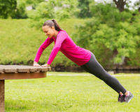 Smiling woman doing push-ups on bench outdoors Stock Photography