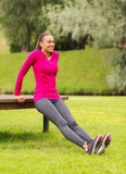 Smiling woman doing push-ups on bench outdoors Royalty Free Stock Images