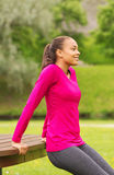 Smiling woman doing push-ups on bench outdoors Stock Images