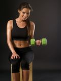 Smiling woman doing seated dumbbell curl. Photo of an attractive female doing a dumbbell curl while sitting Stock Photography