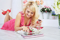 Smiling woman doing shopping online on touchpad. Portrait of smiling young Caucasian blond woman wearing dress lying on pillow at home and using digital tablet Royalty Free Stock Photo