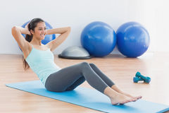 Smiling woman doing sit ups in fitness studio Stock Image