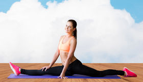 Smiling woman doing splits on mat over cloud Royalty Free Stock Images