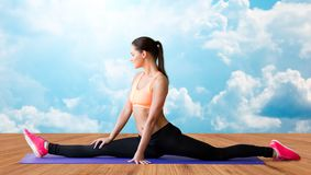 Smiling woman doing splits on mat over clouds Stock Photos