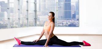 Smiling woman doing splits on mat over gym Stock Photography