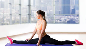 Smiling woman doing splits on mat over gym Stock Photos