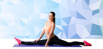 Smiling woman doing splits on mat over low poly Royalty Free Stock Photo